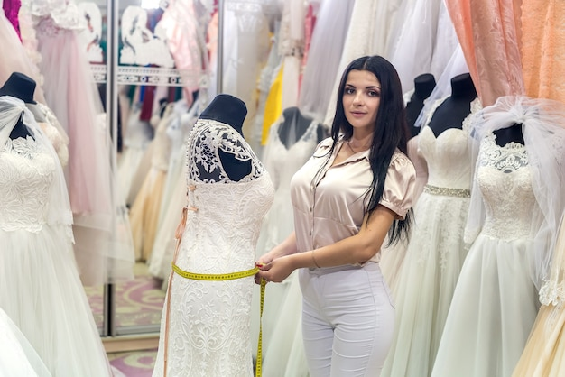 Costureira medindo cintura em vestido de noiva em salão
