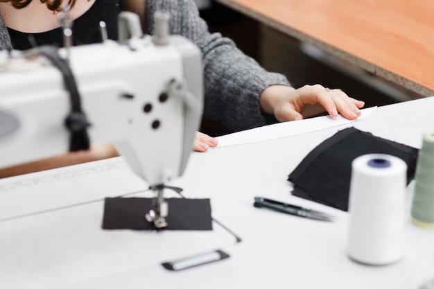 Costureira medindo o número necessário de tecido.