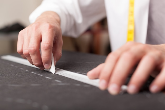 Costureira medindo o padrão do alfaiate no fundo