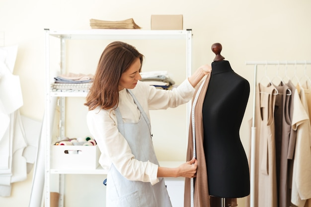 Costureira moreno no avental que mede o tecido bonito no manequim preto na oficina