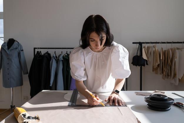 Costureira mulher desenha padrões e mede o material na mesa no conceito de indústria de vestuário do ateliê