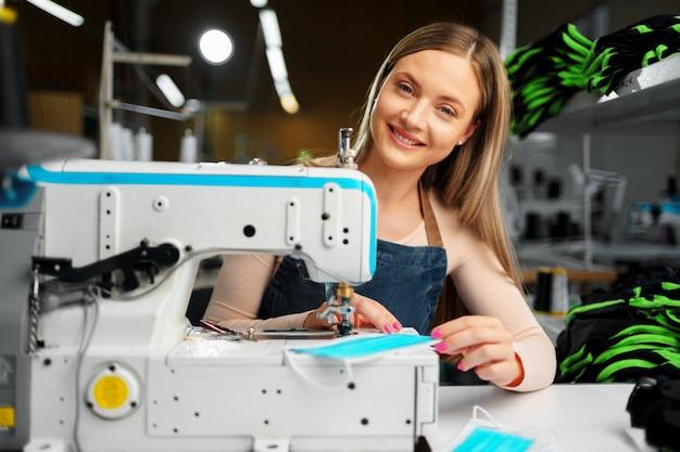 Costureira mulher no local de trabalho que costura roupas na máquina de costura