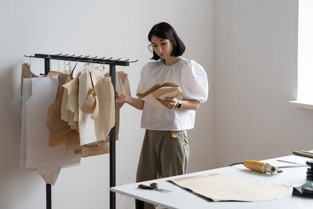 Costureira mulher segura padrão para roupas no ateliê de estilista inspiradora para o trabalho no estúdio