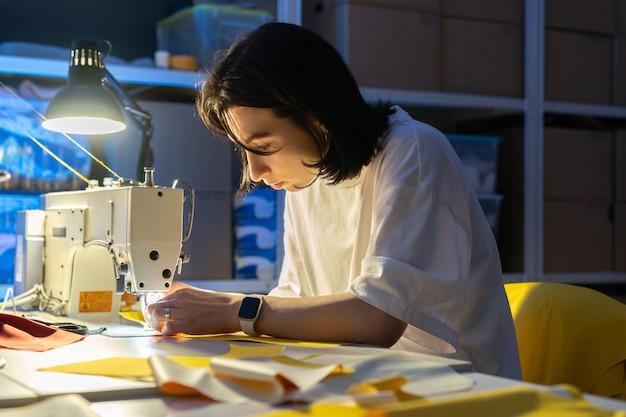 Costureira mulher trabalhando na máquina de costura costurar roupas criar uma nova coleção conceito de pequena empresa
