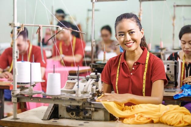 Costureira na fábrica têxtil sorrindo enquanto costura com industrial
