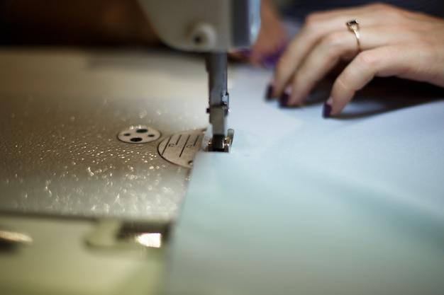 Costureira no local de trabalho, indústria de costura, garota costura na máquina de costura, roupas de fábrica,
