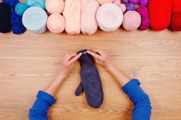 Costureira no local de trabalho. mãos femininas menina mulher tricotando luvas quentes por agulhas de malha com linha de bolas de fio