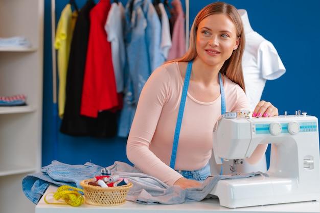 Costureira nova que trabalha em sua máquina de costura na fábrica de matéria têxtil