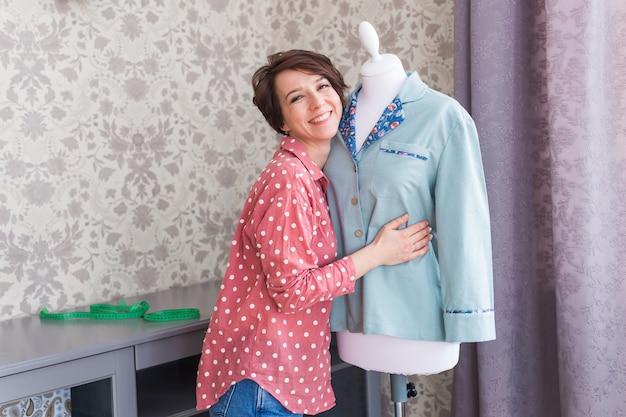 Costureira ou alfaiate segurando uma camisa no manequim no estúdio de design criativo doméstico