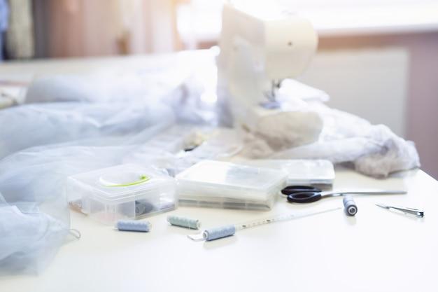 Costureira ou costureira no local de trabalho com máquina de costura, linhas e tesouras na mesa, close-up, fundo de luz solar