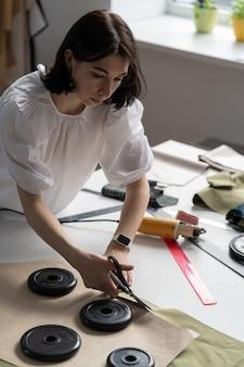 Costureira profissional segurando uma tesoura, cortando o material na mesa no ateliê, alfaiate, no estúdio