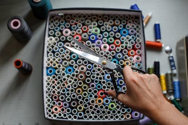 Costureira puxa uma tesoura de uma caixa com novelos de fios coloridos