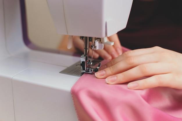Costureira sentada e costurando na máquina de costura