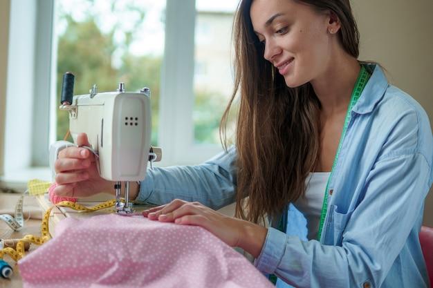 Costureira sorridente feliz com máquina de costura elétrica e acessórios de costura diferentes para costurar roupas no local de trabalho