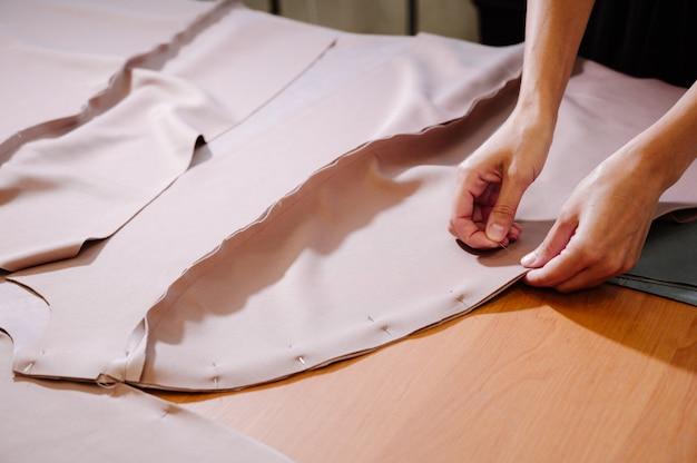 Costureira tecido vestido de costura com as mãos