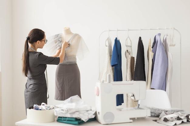 Costureira, tecnologias, estilista e conceito de alfaiate - jovem estilista trabalhando em seu showroom
