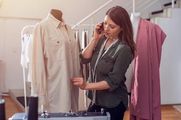 Costureira trabalha com roupas novas encomendadas pelo cliente da internet