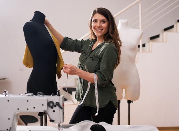 Costureira trabalha com roupas novas encomendadas por um cliente em uma loja
