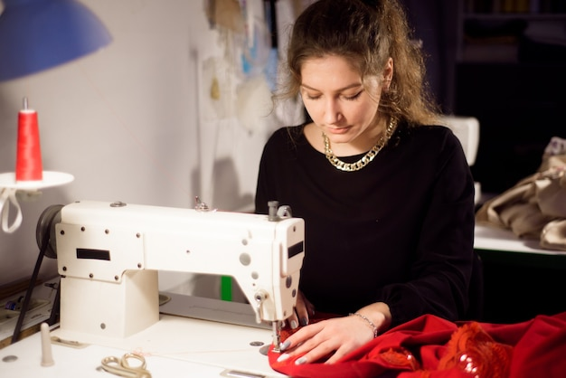 Costureira trabalhando na máquina de costura. alfaiate fazendo uma vestimenta. costura de passatempo como um conceito de empresa de pequeno porte.