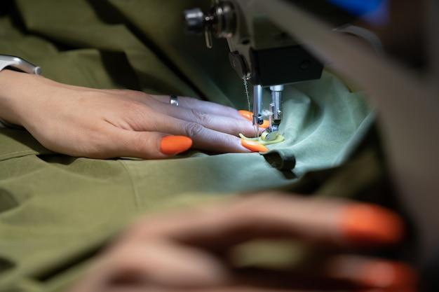 Costureira trabalhando na máquina de costura closeup mulher estilista cria nova coleção de roupas