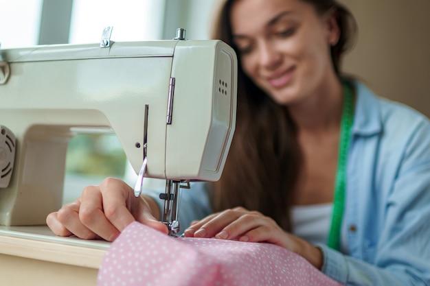 Costureira usando máquina de costura elétrica e diferentes acessórios de costura para costurar roupas