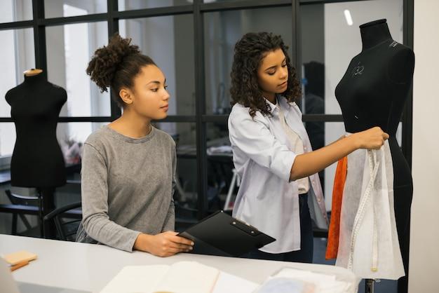 Costureiro jovem e alfaiate trabalhando juntos no atelier, aprendendo o design de moda