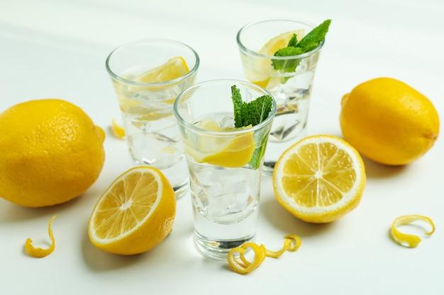 Cotas de vodka e limões em fundo branco