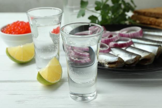 Cotas de vodka e petiscos saborosos em fundo branco de madeira, close-up