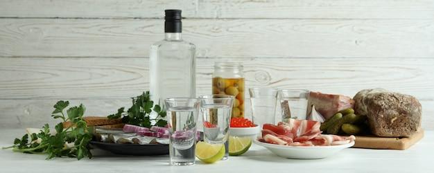 Cotas de vodka e petiscos saborosos em fundo branco de madeira