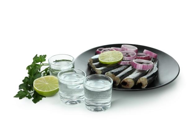 Cotas de vodka e petiscos saborosos isolados no fundo branco