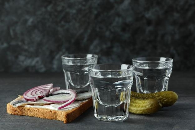 Cotas de vodka e petiscos saborosos na mesa de madeira escura