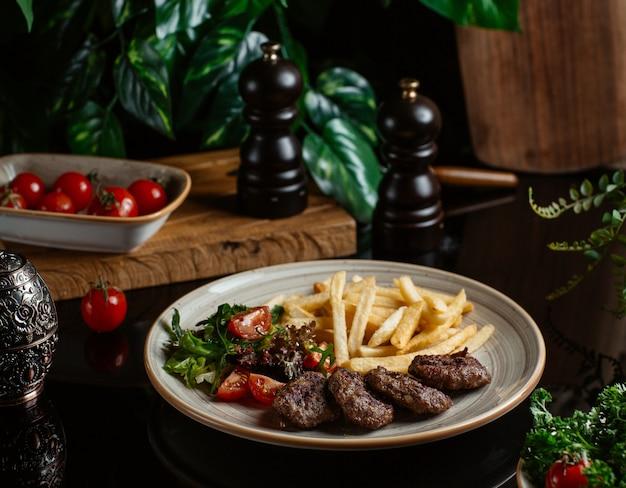 Cotlet de carne com salada de legumes e palitos de batata.