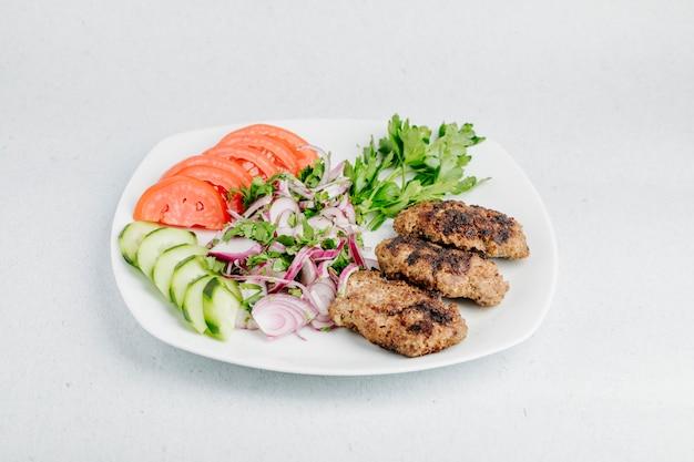 Cotlet de frango com legumes e salada verde.