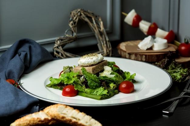 Cotlet de peixe servido com salada de alface, pão integral e tomate