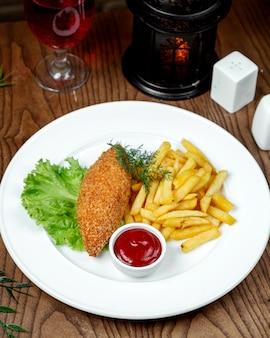 Cotlete de kiev com batatas fritas em cima da mesa