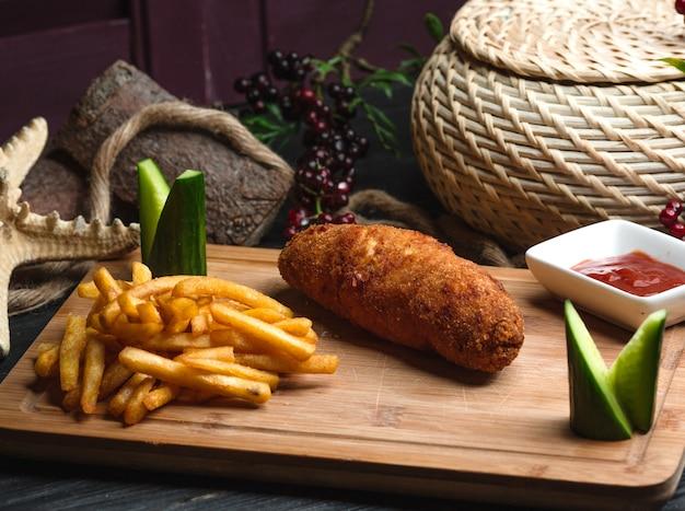 Cotlete de kiev com batatas fritas na placa de madeira