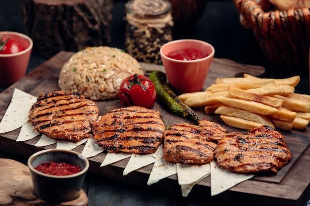 Cotlets de frango com batatas fritas, legumes grelhados e guarnição de arroz.