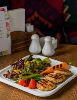 Cotlets de frango com cenoura grelhada e salada verde.