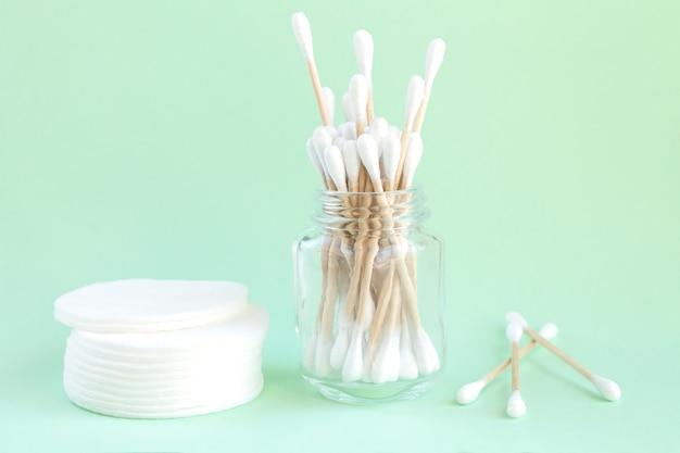 Cotonetes de bambu orgânico em frasco de vidro e almofadas de algodão para vista superior da higiene pessoal
