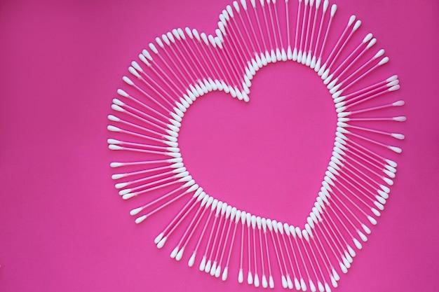 Cotonetes dispostas em forma de um coração em um fundo rosa