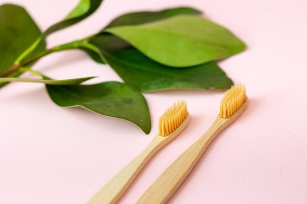 Cotonetes e almofadas de algodão para higiene humana diária, a mão de uma mulher segurando escovas de dente de bambu em uma rosa