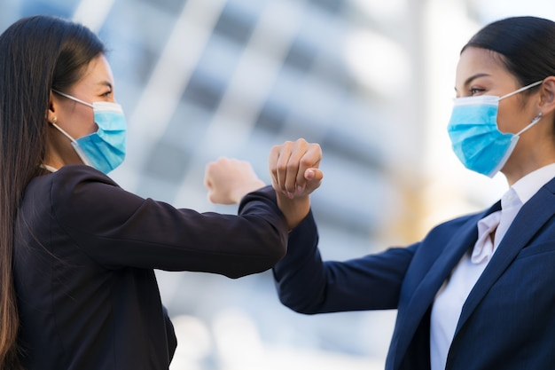 Cotovelo batendo, novo normal, colegas usando máscaras de proteção e cumprimentando cotovelos batendo
