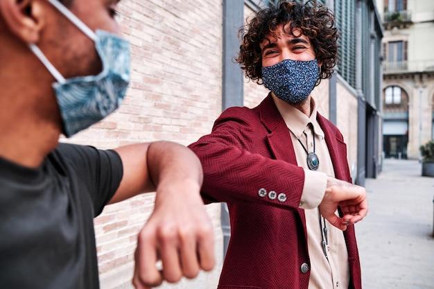 Cotovelo batendo. saudação do cotovelo para evitar a propagação do coronavírus (covid-19). homens de camisa se encontram na rua com as mãos nuas. em vez de cumprimentar com um aperto de mão ou um abraço, eles batem nos cotovelos