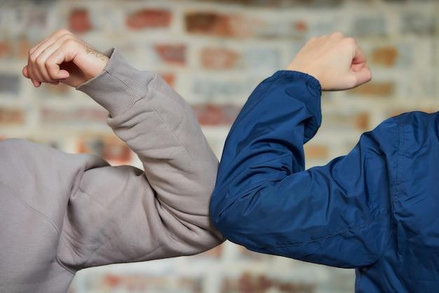 Cotovelo batendo. uma nova maneira de cumprimentar para evitar a propagação do coronavírus (covid-19). um menino e uma menina batem nos cotovelos em vez de cumprimentar com um abraço ou um aperto de mão contra uma parede de tijolos.