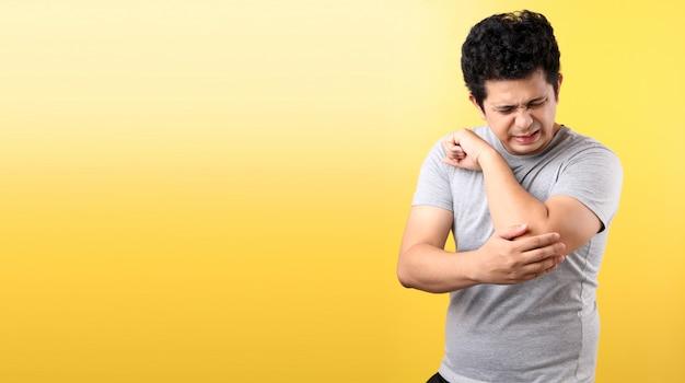Cotovelo tocante do homem asiático considerável com expressão facial dolorosa na parede amarela.