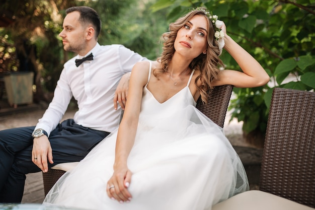 Coupe recém-casado sentado em um sofá com raiva um do outro em um meio de um argumento