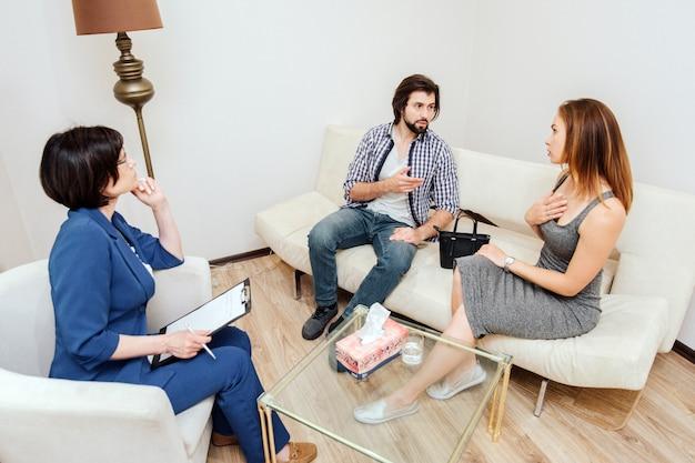 Couplt está sentado e conversando. homem está apontando na mulher. ela está apontando para si mesma. médico está ouvindo-os com muito cuidado.