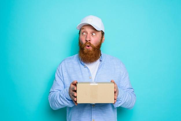 Courier com caixa de papelão na mão fica surpreso com algo