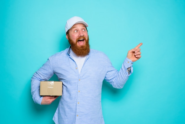 Courier com caixa de papelão na mão fica surpreso e indica algo
