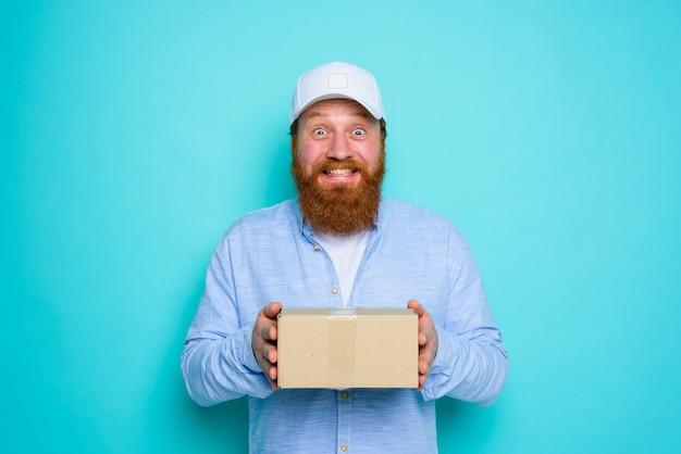 Courier com chapéu fica feliz em entregar uma caixa de papelão